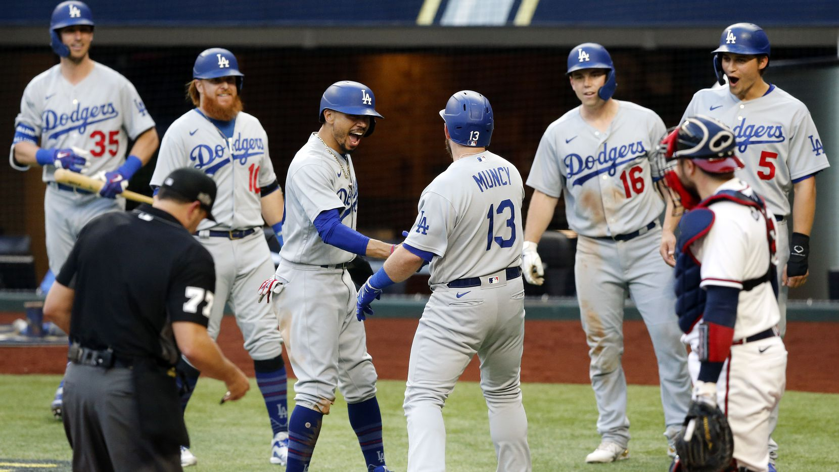 Los Angeles Dodgers first baseman Max Muncy (13) is welcomed to home plate by his teammates after his first inning grand slam in Game 3 of the National League Championship Series at Globe Life Field in Arlington, Wednesday, October 14, 2020. (from left) Los Angeles Dodgers Cody Bellinger (35), Justin Turner (10), Mookie Betts (50), Will Smith (16) and Corey Seager (5) are part of the 11-run first celebration. (Tom Fox/The Dallas Morning News)