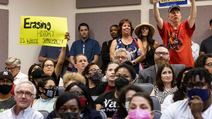 """A community member holds a """"Erasing history is white supremacy"""" sign as someone holds a """"Stop critical race theory"""" sign on Tuesday, June 22, 2021, during the Fort Worth ISD board meeting in Fort Worth. (Juan Figueroa/The Dallas Morning News)"""