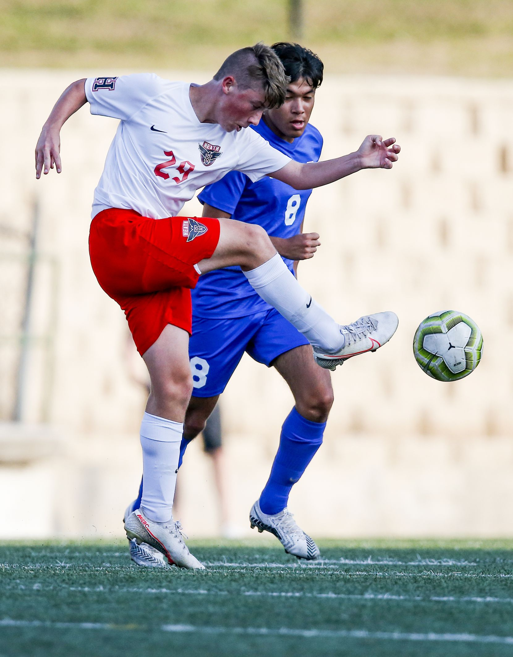 Rockwall-Heath freshman midfielder Andrew Cooley (29) and Allen senior midfielder Isaiah Moreno (8) battle for the ball during the first half of a boys soccer Class 6A state semifinal at Mesquite Memorial Stadium in Mesquite, Tuesday, April 13, 2021. (Brandon Wade/Special Contributor)