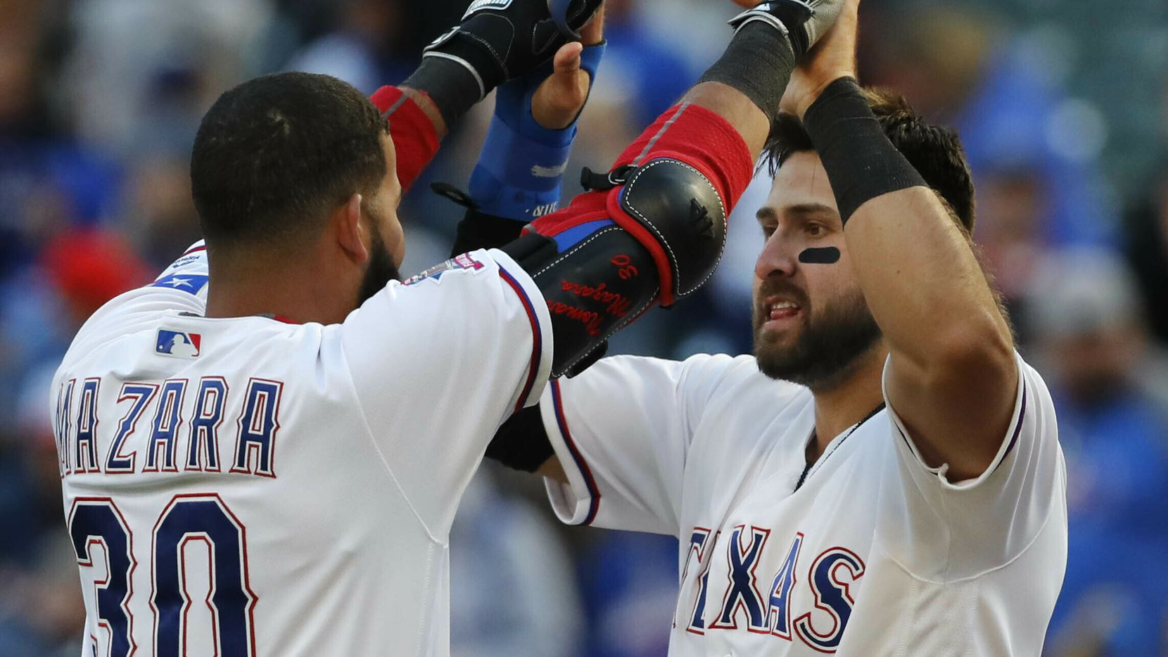Texas Rangers Joey Gallo, right, is congratulated by teammate Nomar Mazara (30) after scoring the game winning run during the ninth inning of a baseball game against the Chicago Cubs in Arlington,Texas, Sunday, March 31, 2019. (AP Photo/LM Otero)