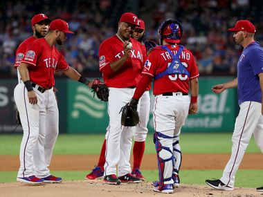 ARLINGTON, TEXAS - SEPTEMBER 24: Manager Chris Woodward #8 of the Texas Rangers pulls Edinson Volquez #36 of the Texas Rangers from the game against the Boston Red Sox in the top of the first inning at Globe Life Park in Arlington on September 24, 2019 in Arlington, Texas.