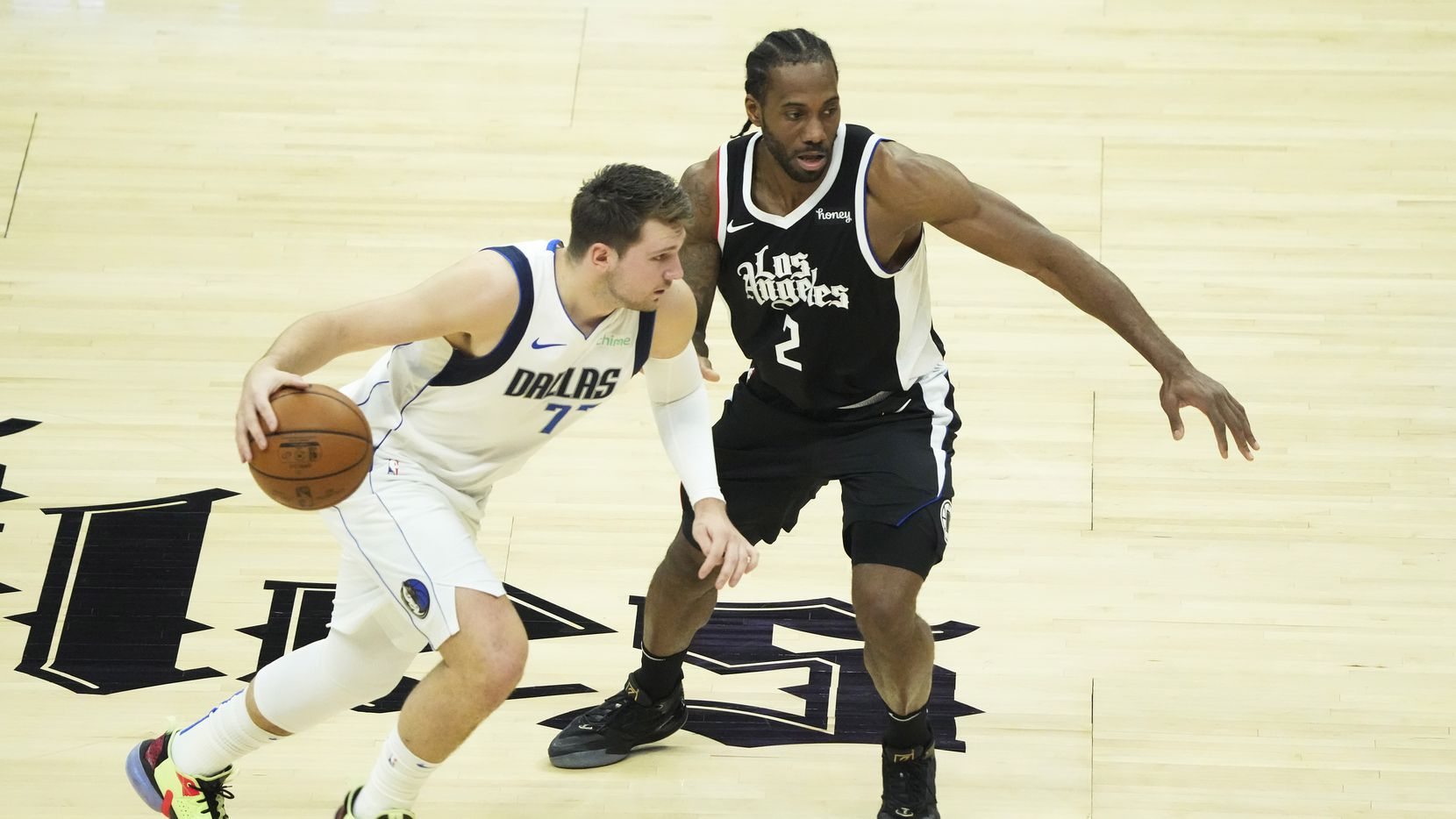 El jugador de los Mavericks de Dallas, Luka Doncic (izq), es custodiado por Kawhi Leonard, de los Clippers de Los Ángeles en un partido de playoffs, el 6 de junio de 2021 en el Staple center de Los Ángeles.