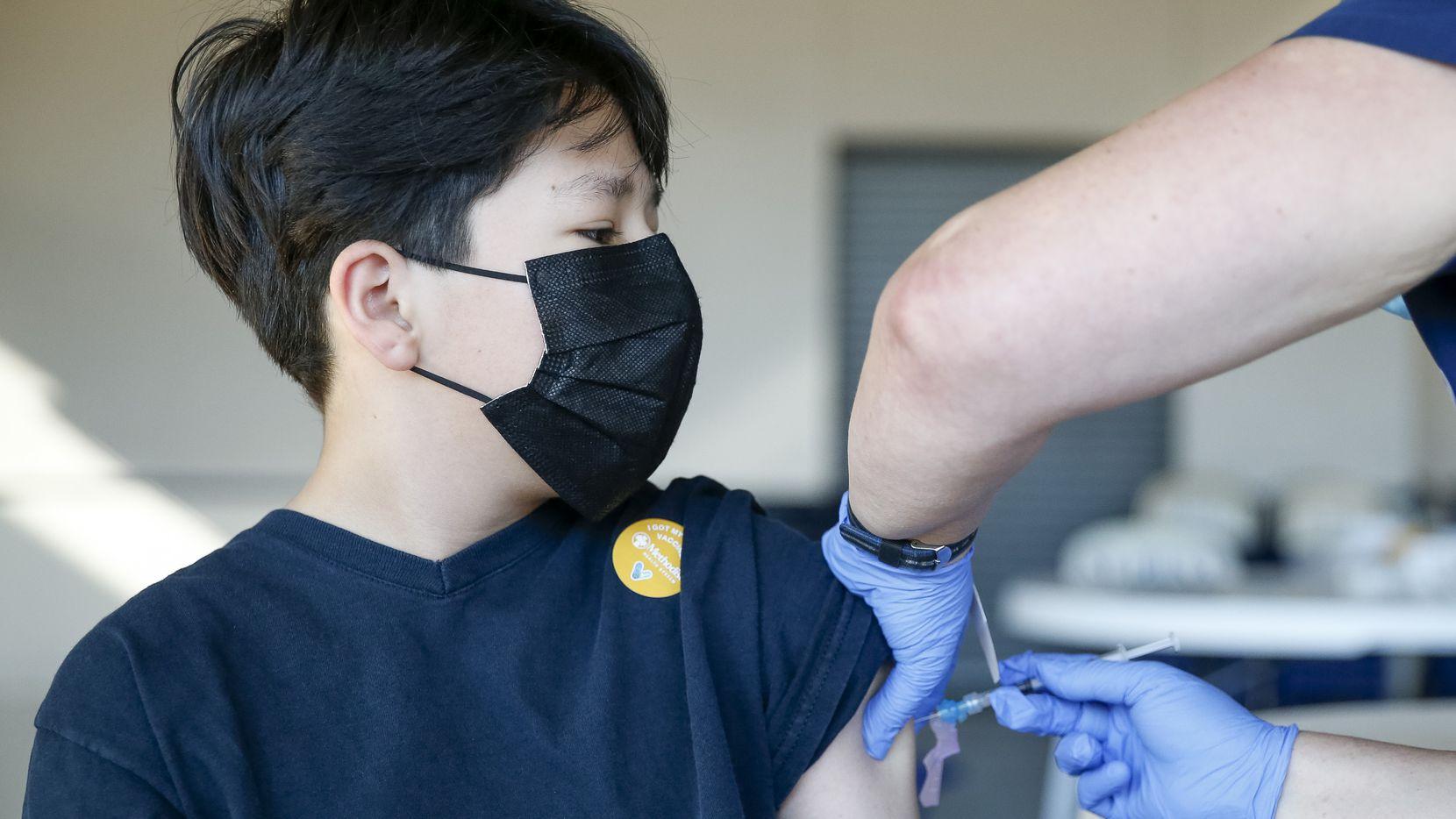 Jancarlo Aguado, de 13 años, recibe una dosis de Pfizer contra covid-19 en una clínica organizada en St. Pius X, el sábado pasado.
