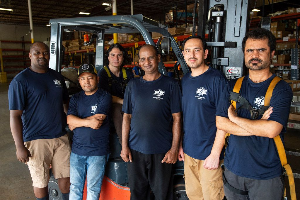 Elliott Electric Supply refugee employees Emmanuel Habumremyi, Hussain Aklaqi, Asif Ali, Shafqat Masih, Muzamil Mehdi and Abdul Fazal, left to right, pose for a portrait in the regional distribution center where they work Wednesday, July 3, 2019 in Farmers Branch, Texas.  Elliott Electric Supply has partnered with Amplio Recruiting, a staffing agency that connects companies with refugees seeking employment, to hire several refugees to work in their distribution center.  (Jeffrey McWhorter/Special Contributor)