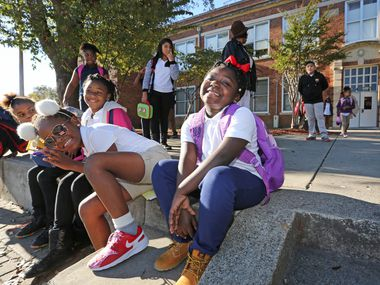 Students Ramya Norman, Tamiah Brown, Kanayia Williams and D'Corria Hamilton, right to left, wait for their rides home as students get out of school at the Charles Rice Learning Center on Pine Street in Dallas on Wednesday, November 29, 2016.