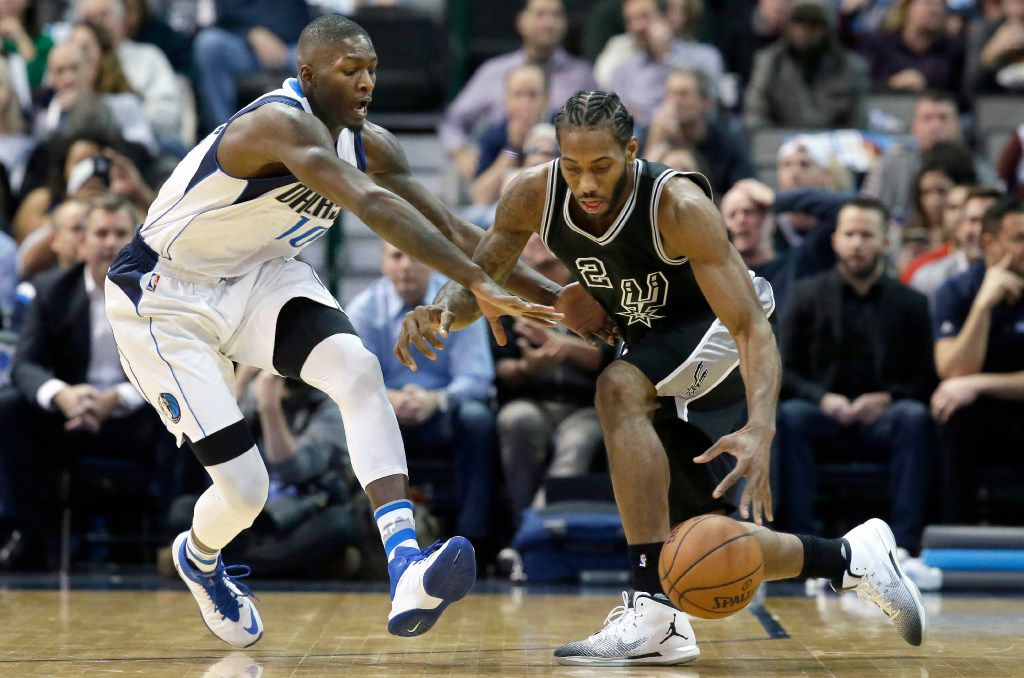 San Antonio Spurs forward Kawhi Leonard (2) dribbles against Dallas Mavericks forward Dorian Finney-Smith (10) during the first half of an NBA basketball game in Dallas, Wednesday, Nov. 30, 2016. (AP Photo/LM Otero)