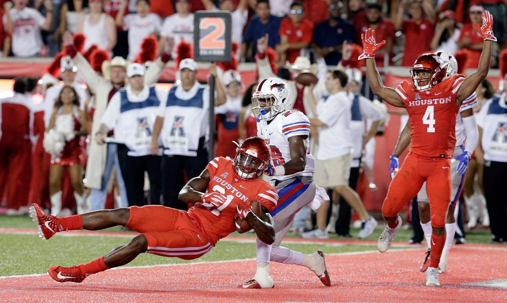 Houston Cougars wide receiver Ellis Jefferson (21) falls into the end zone to score as SMU defensive back Christian Davis (28) defends as D'Eriq King celebrates in the first half of an NCAA college football game Saturday, Oct. 7, 2017, in Houston. (AP Photo/Michael Wyke)