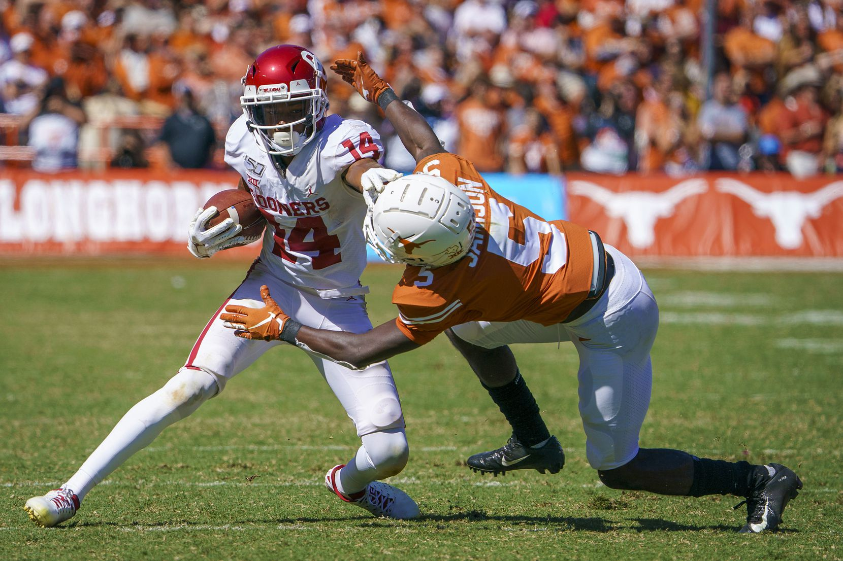 Oklahoma wide receiver Charleston Rambo (14) pushes off of Texas defensive back D'Shawn Jamison (5) during the second half of an NCAA football game at the Cotton Bowl on Saturday, Oct. 12, 2019, in Dallas.