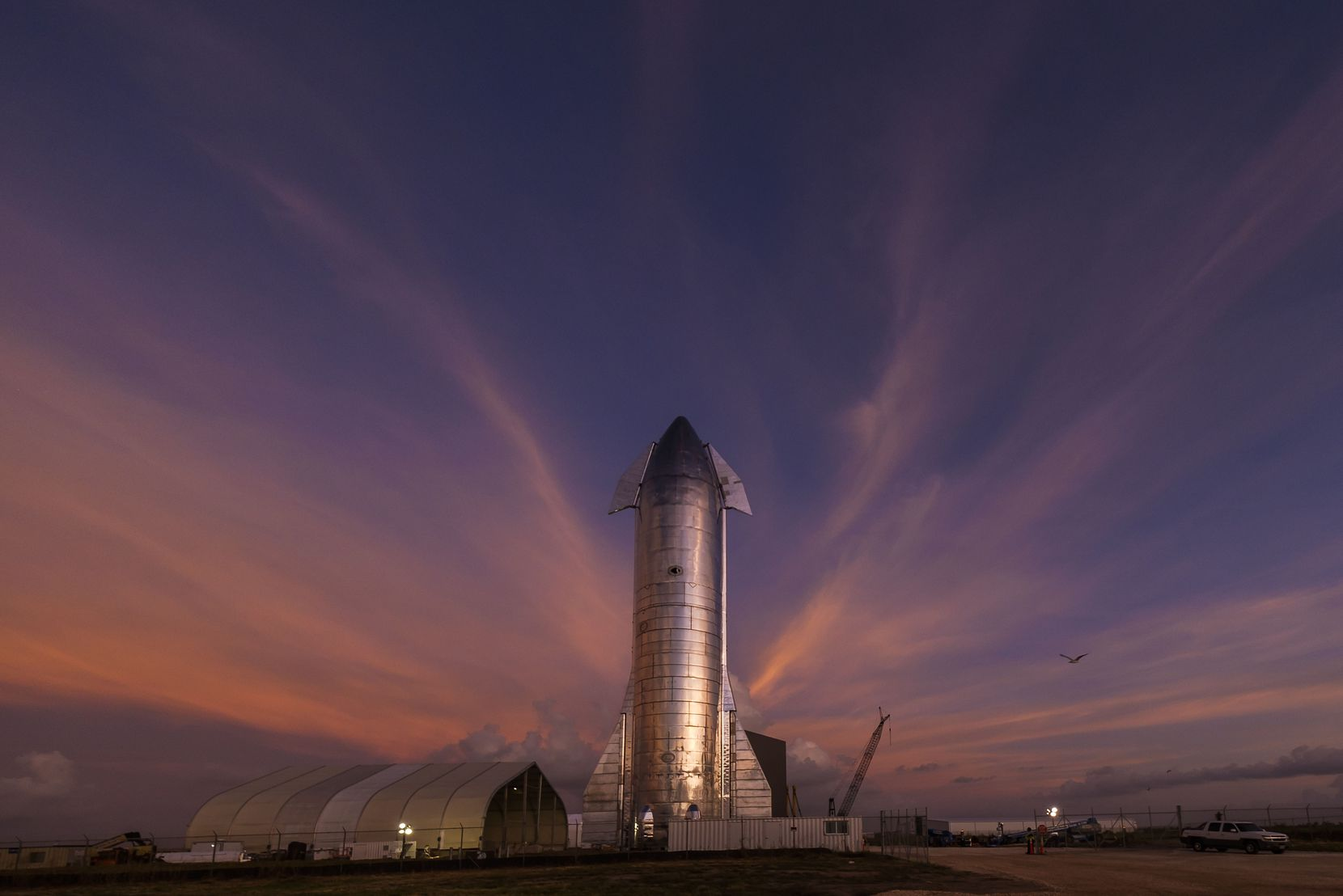 The sky begins to light up before sunrise over a prototype of the SpaceX Starship at the SpaceX launch facility in Boca Chica.