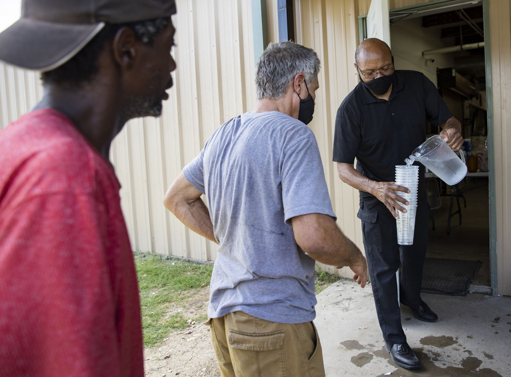 Pastor Chris Simmons hands out ice cold water to Cornerstone clients.