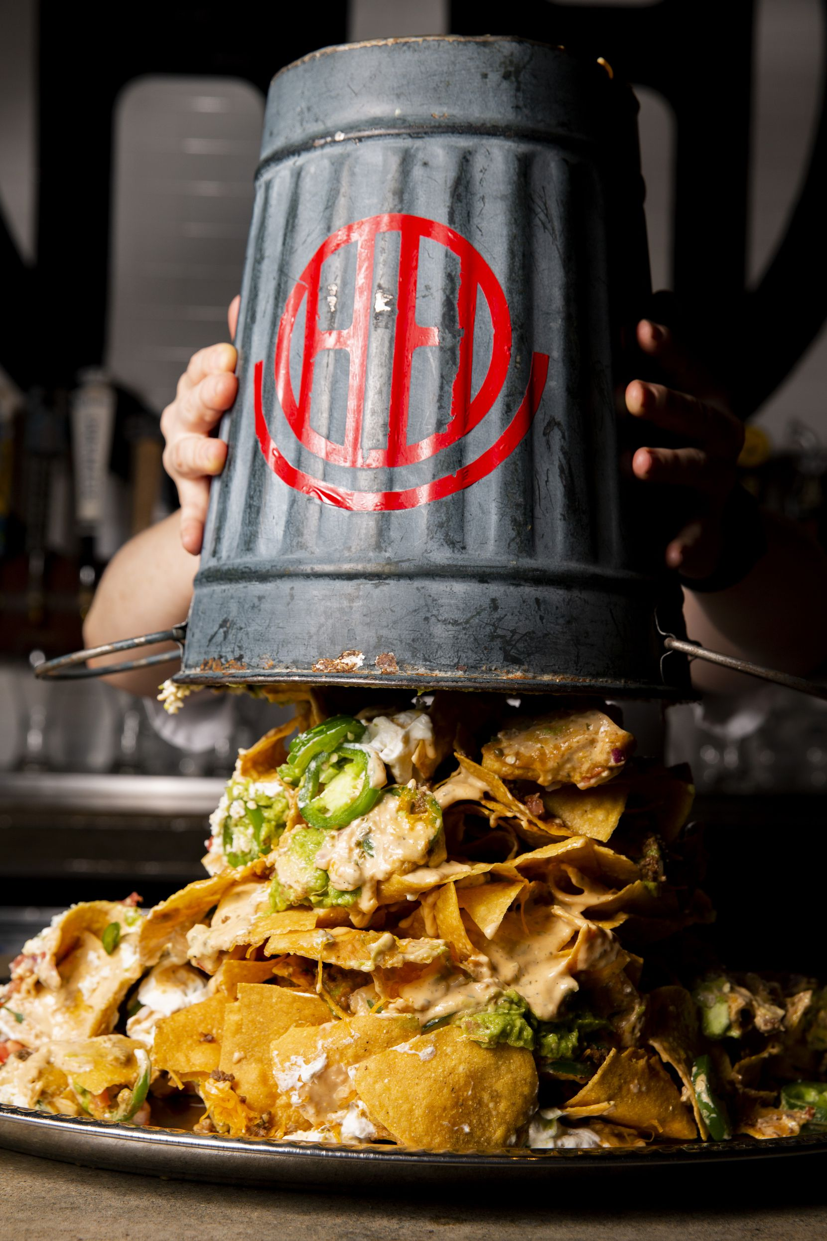 The nacho tower at Happiest Hour comes with chips, cheese, ground beef, guacamole and more, stacked in a bucket and then unleashed onto a massive silver platter. The effort is done tableside — and the whole room watches.