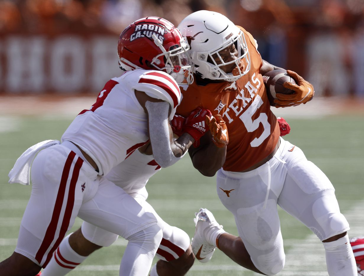 Texas Longhorns running back Bijan Robinson (5) is pushed out of bounds by Louisiana-Lafayette Ragin Cajuns safety Percy Butler (9) during the first quarter at DKR-Texas Memorial Stadium in Austin, Saturday, September 4, 2021.(Tom Fox/The Dallas Morning News)