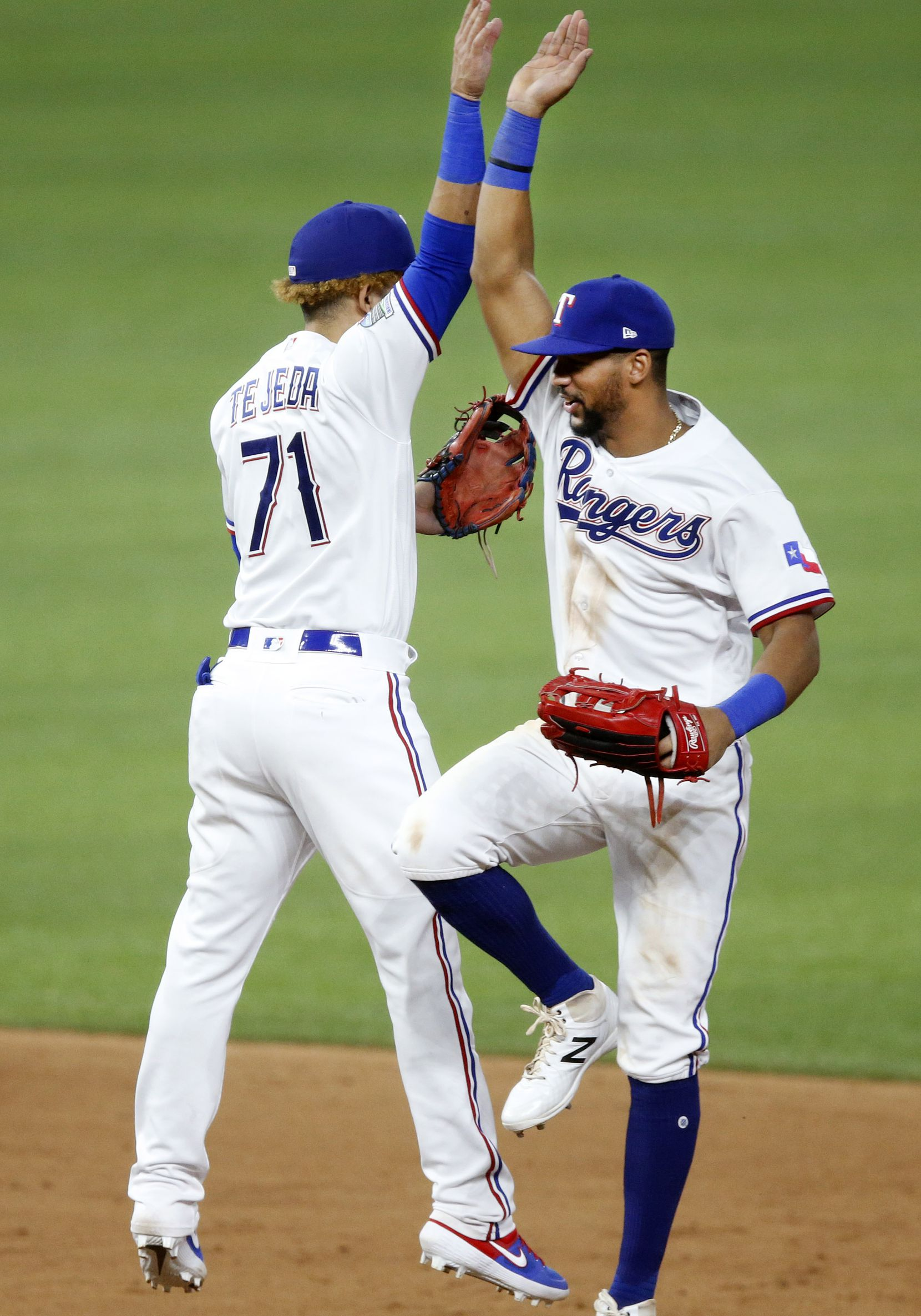 Texas Rangers second basemen Anderson Tejeda (71) and center fielder Leody Taveras high-five after they beat the Los Angeles Angels, 7-1, at Globe Life Field in Arlington, Texas, Tuesday, September 8, 2020. (Tom Fox/The Dallas Morning News)
