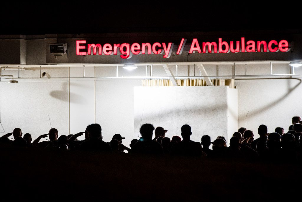 California Highway Patrol Officers gather outside the emergency room entrance to the Riverside University Health System Medical Center in Moreno Valley, Calif., on Monday, Aug 12, 2019, after an officer was killed in a shootout following a traffic stop in Riverside.