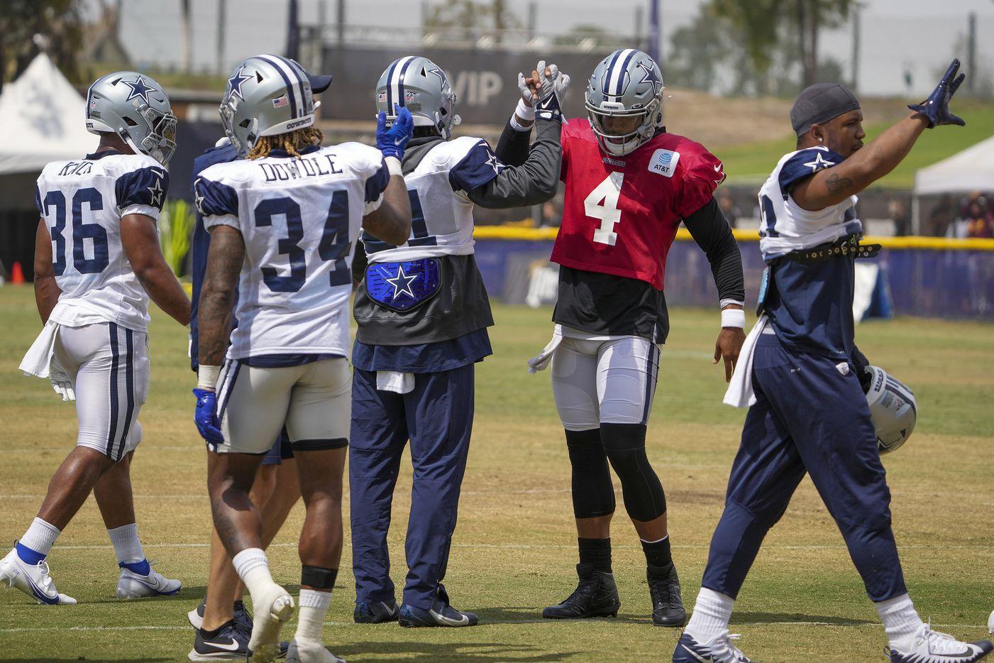 Dallas Cowboys quarterback Dak Prescott (4) does a dance with running back Ezekiel Elliott (21) during a practice at training camp on Wednesday, Aug. 11, 2021, in Oxnard, Calif.