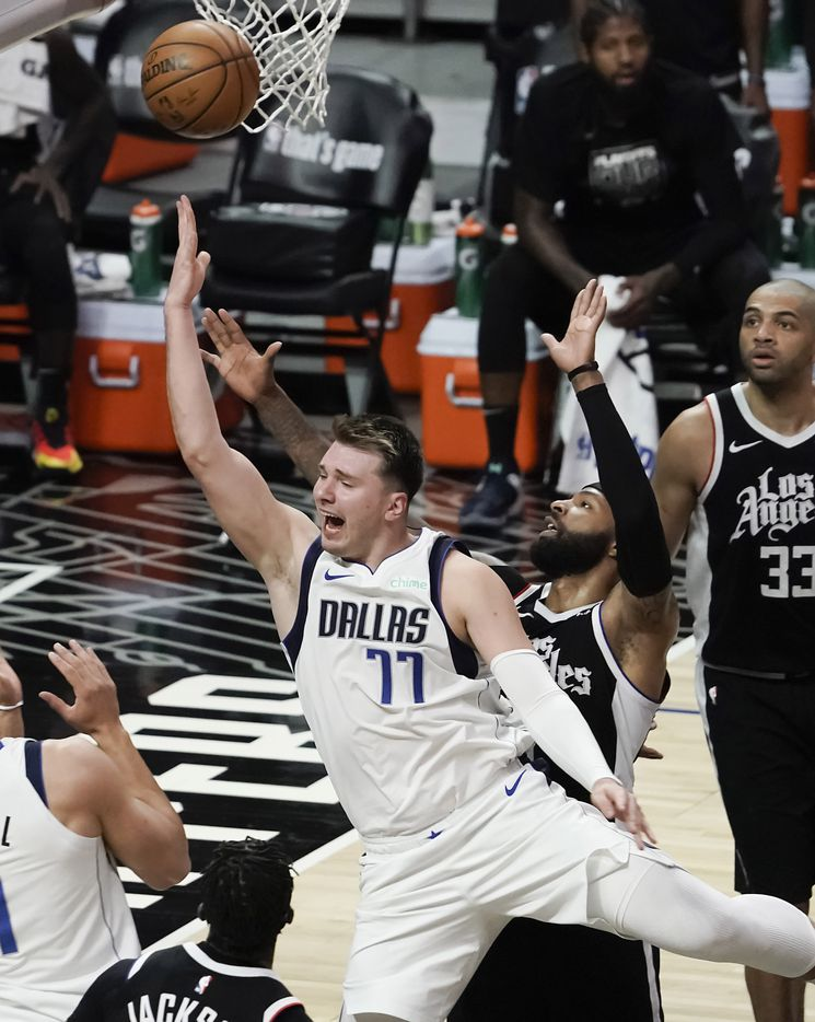 Dallas Mavericks guard Luka Doncic (77) drives to the basket past LA Clippers forward Marcus Morris Sr. (8) and forward Nicolas Batum (33) during the second half of an NBA playoff basketball game at Staples Center on Saturday, May 22, 2021, in Los Angeles.