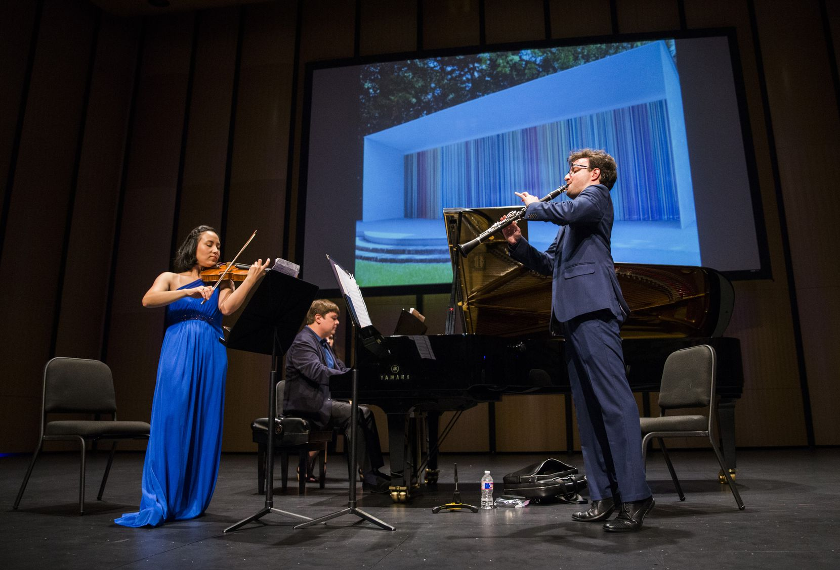 "Violinist Grace Kang Wollett, pianist Mikhail Berestnev and clarinetist Danny Goldman rehearse under a photo of ""Horizons,"" artwork by Ian Davenport, before a Basically Beethoven Festival concert on July 7, 2019, at Moody Performance Hall in Dallas."