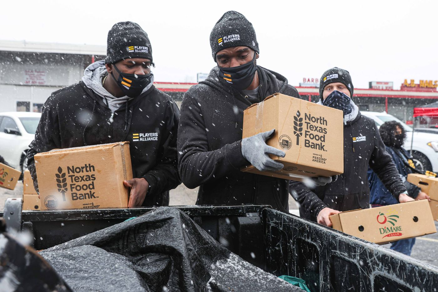 From left, pitchers for the Texas Rangers, DeMarcus Evans and Taylor Hearn, place boxes of food in the truck of a car as part of the donations made by the MLB Players Alliance in Oak Cliff on Sunday, January 10, 2021.