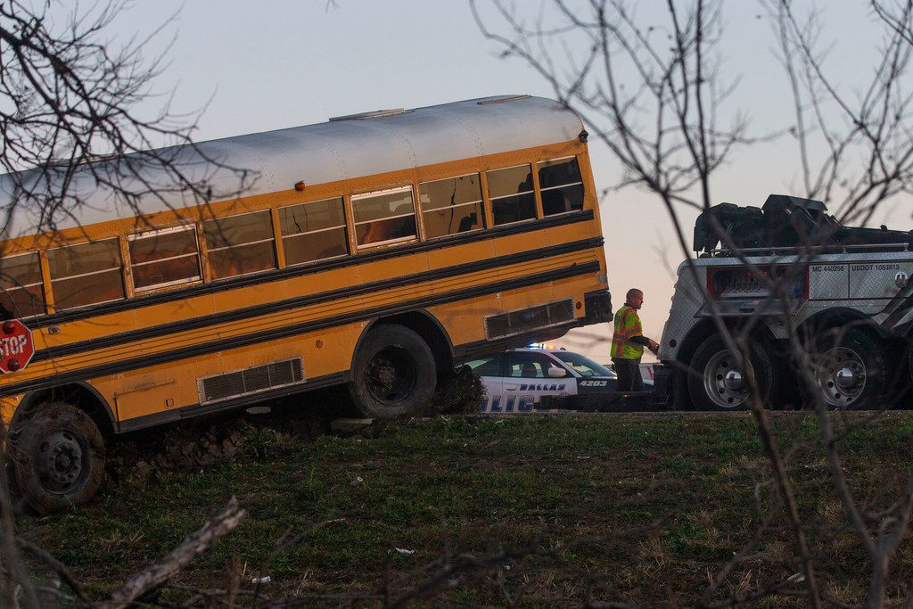 A school bus from Bishop Dunne Catholic School overturned in the westbound lanes of I-30 near Loop 12 in Dallas on Thursday.  (Shaban Athuman/The Dallas Morning News)