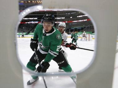 Dallas Stars left wing Jason Robertson (21) and Chicago Blackhawks center Pius Suter (24) go after the puck during the first period of play at American Airlines Center on Tuesday, February 9, 2021in Dallas.
