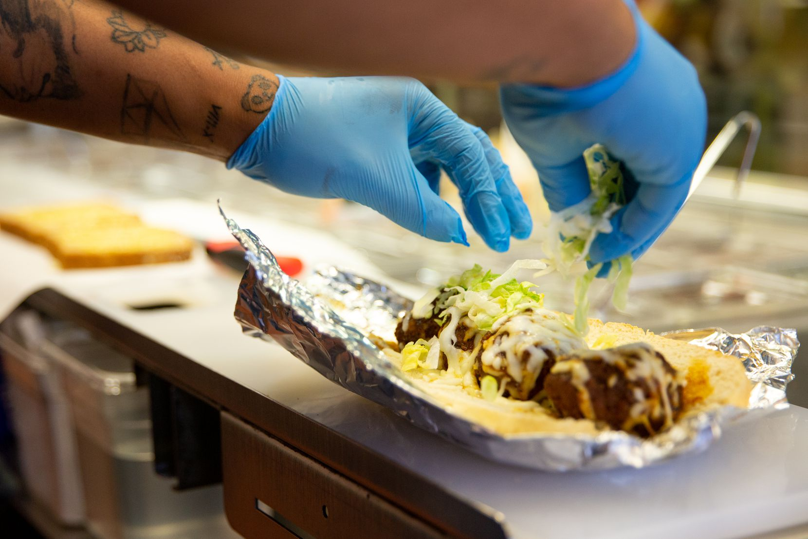 An employee sprinkles lettuce onto a meatball sub at Patriot Sandwich Company in Denton.