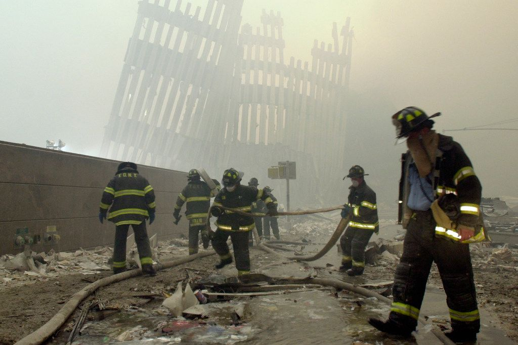 In this Sept. 11, 2001, photo, firefighters work beneath the destroyed vertical struts that once faced the outer walls of the World Trade Center towers, after a terrorist attack on the twin towers in New York. Sept. 11, 2001.