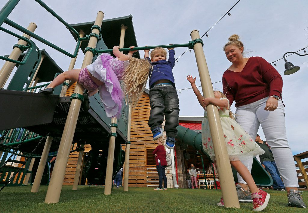 Rebecca Priddy, right, and her children Grace, 5, left, Jacob, 2, second from left, and Charlotte, 3, play at the playground at Hat Creek Burger Company in McKinney, Texas, Tuesday, March 20, 2018. (Jae S. Lee/The Dallas Morning News)