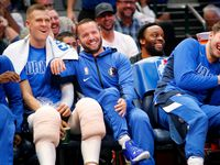 FILE - Mavericks guard J.J. Barea (center) sprung up off the bench in the fourth quarter as if he was going into the game. Here, he laughs with teammates Kristaps Porzingis (left) and Luka Doncic (right) after they were surprised by the move at American Airlines Center in Dallas on Wednesday, Nov. 20, 2019.