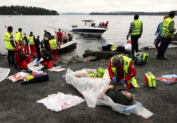 Emegency workers tend to victims on the lakeshore as a boat brings more wounded from Utaøya Island on July 22, 2011, in Norway. Anders Behring Breivik has confessed to killing 69 people in an attack on the Labor Party's youth camp on the island.