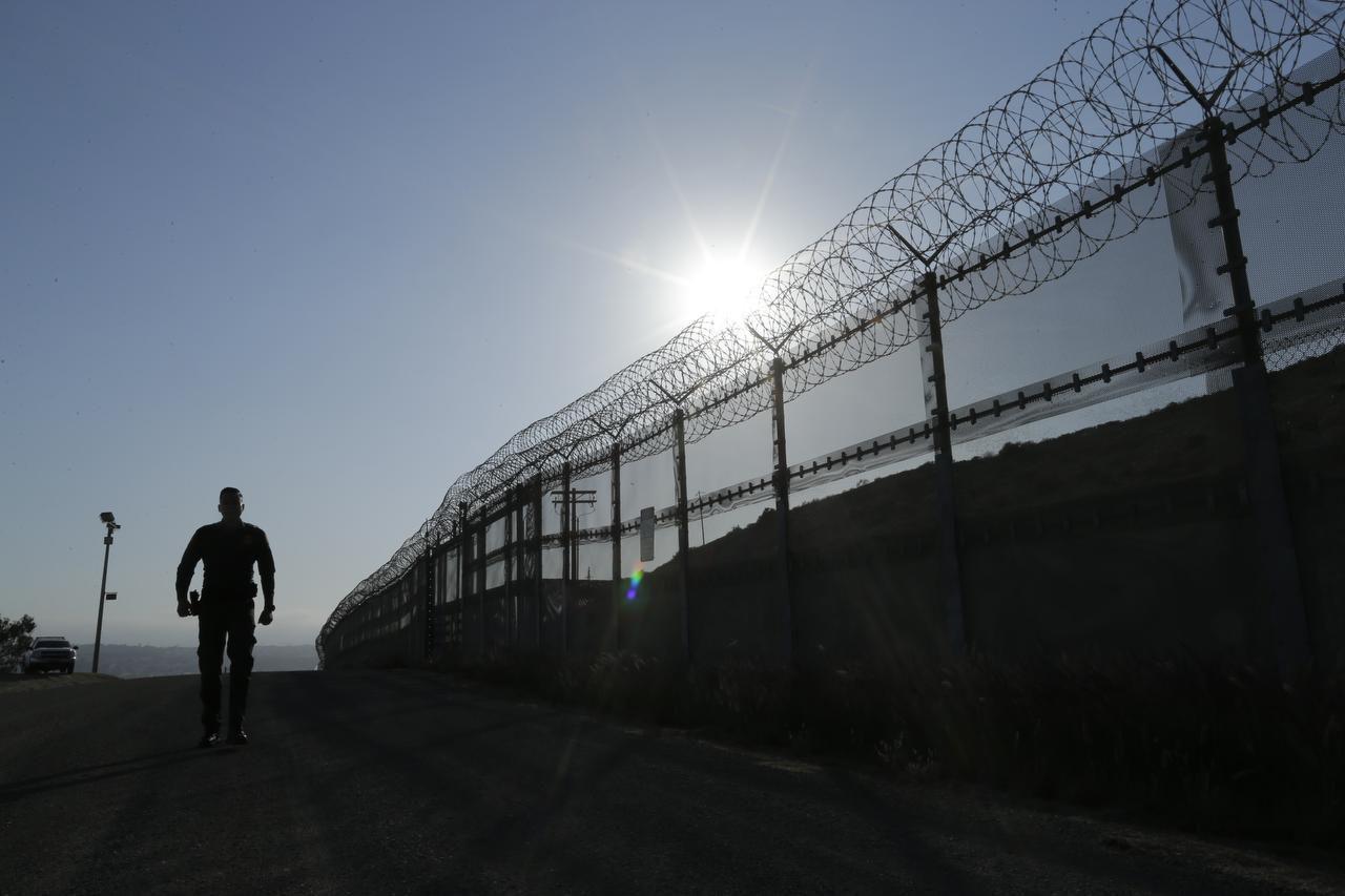 Un agente de la Patrulla Fronteriza camina por la valla de la frontera en San Diego, California el 22 de enero de 2016. (AP/GREGORY BULL)