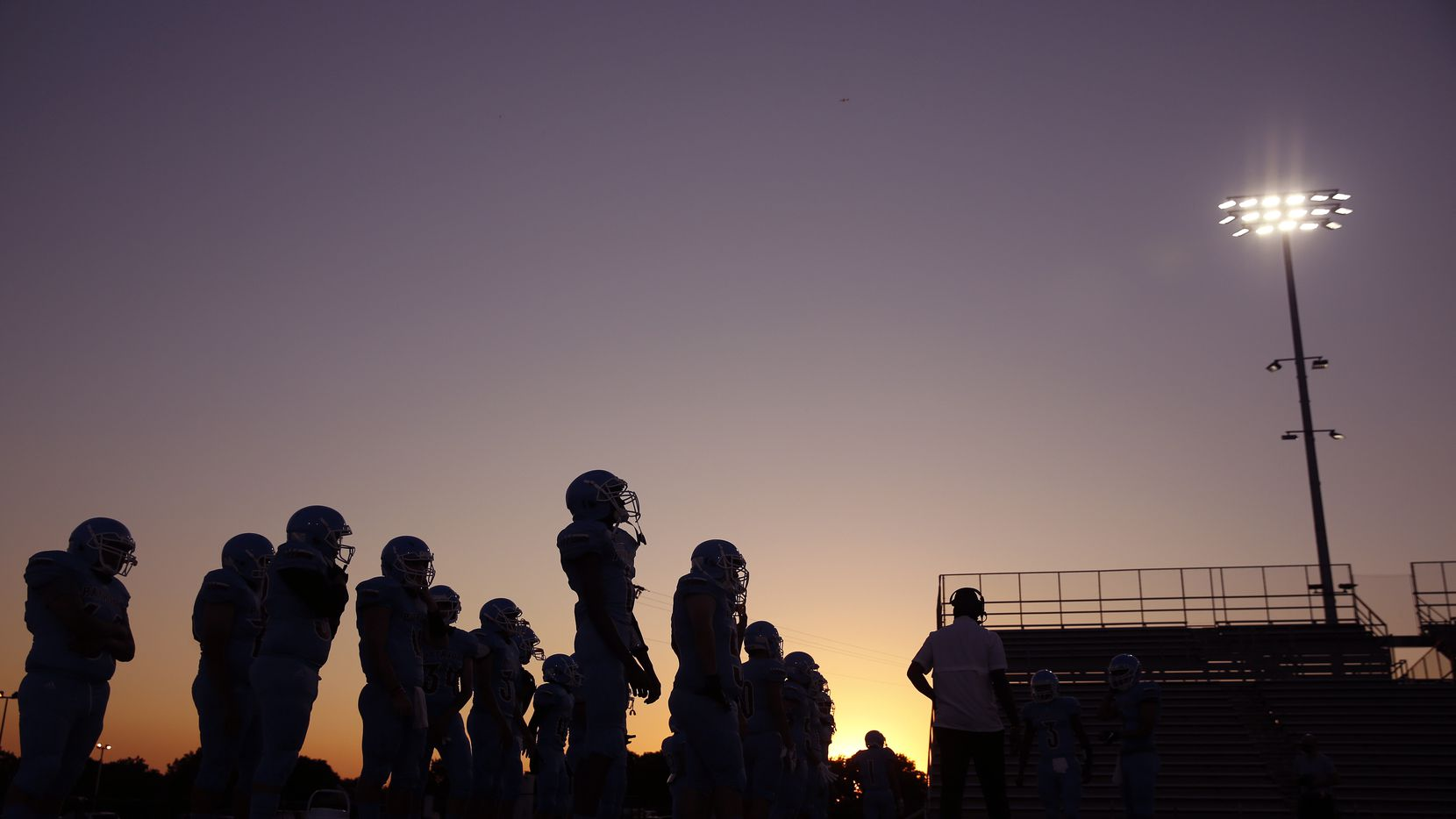 As the sun sets behind Loos Stadium, the Thomas Jefferson football team waits to take the field against Pinkston in Addison, Texas, Thursday, October 1, 2020. This is the first Dallas ISD game of the season.
