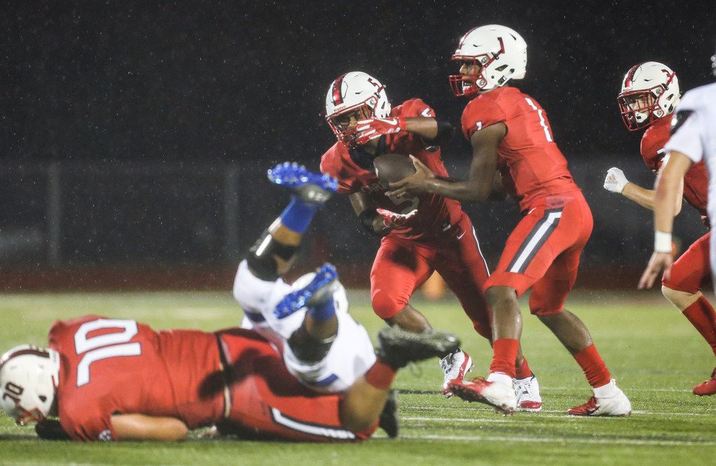 Melissa quarterback Brandon Lewis (1) hands off to running back Ja'Bray Young (5) during a matchup between the Melissa Cardinals and the Trinity Christian-Cedar Hill Tigers on Thursday, Sept. 20, 2018 in Melissa, Texas. (Ryan Michalesko/The Dallas Morning News)