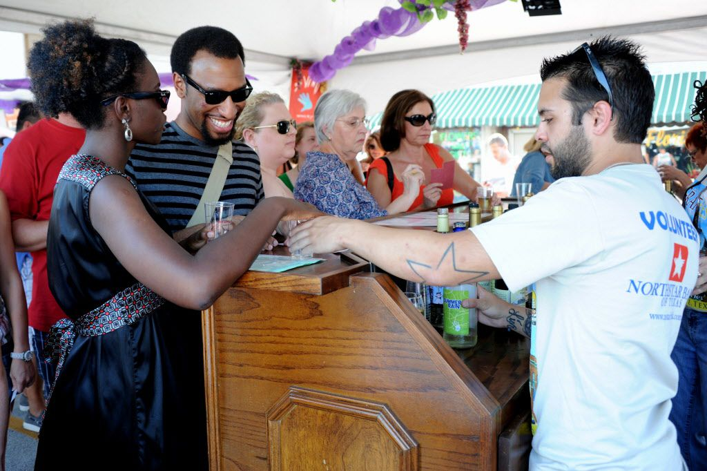 A couple tastes different varietals of red and white wines at GrapeFest on Main Street in Grapevine.