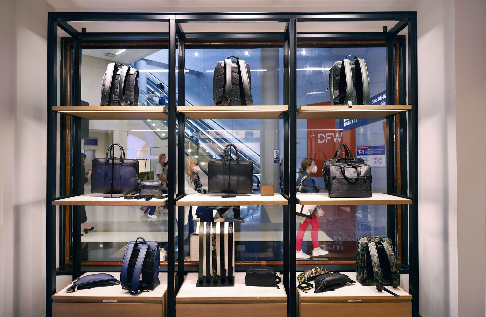 On Friday, travelers walk past a Coach store that showcases handbags and backpacks in Terminal D at DFW Airport.