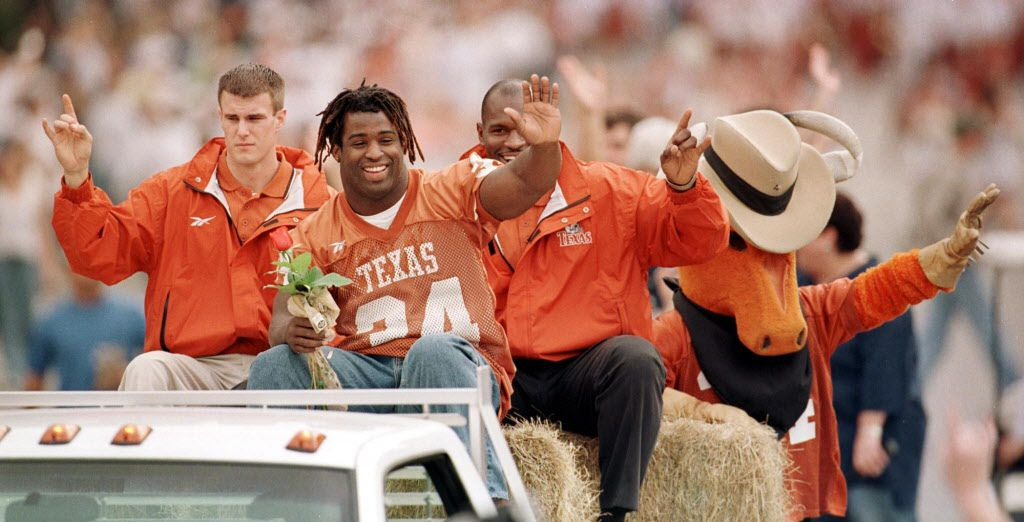 UT football star and Heisman trophy winner Ricky  Williams greets the crowds along Congress Ave. in Austin today as  part of the Parade of Champions honoring the Longhorn football teams success Williams winning the Heisman. (Left behind Ricky is  Tom Herman and right Oscar Giles, both new graduate assistant  football coaches. BY JIM SIGMON