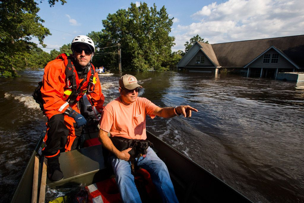 "Captain Jeremy Finney of Tampa Fire and Rescue (left) evacuates Earnest ""Dobie"" Walton from flooding as a result of Tropical Storm Harvey in the Cooks Lake Road area, one of the hardest-hit areas in Hardin County."