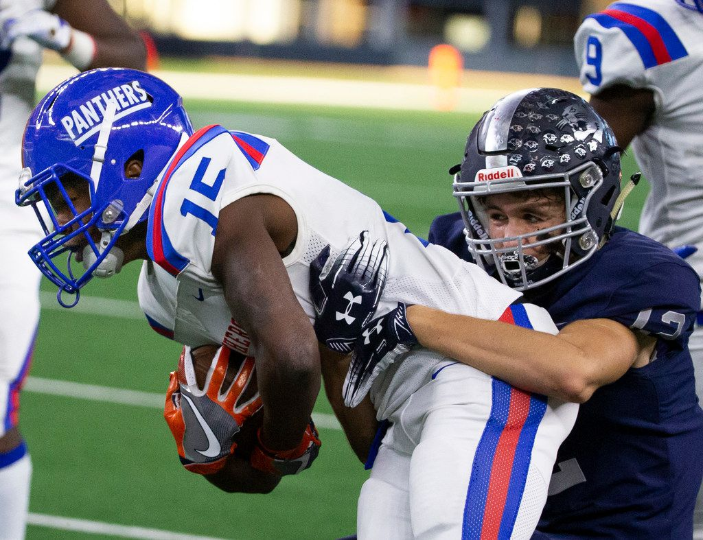 Duncanville defensive back James Roberts Jr. tries to escape the pull of Flower Mound receiver Parker Clark during the first half of the Class 6A Division I area-round high school football playoff game at the AT&T Stadium in Arlington, Texas, on Saturday, November 23, 2019. (Lynda M. Gonzalez/The Dallas Morning News)