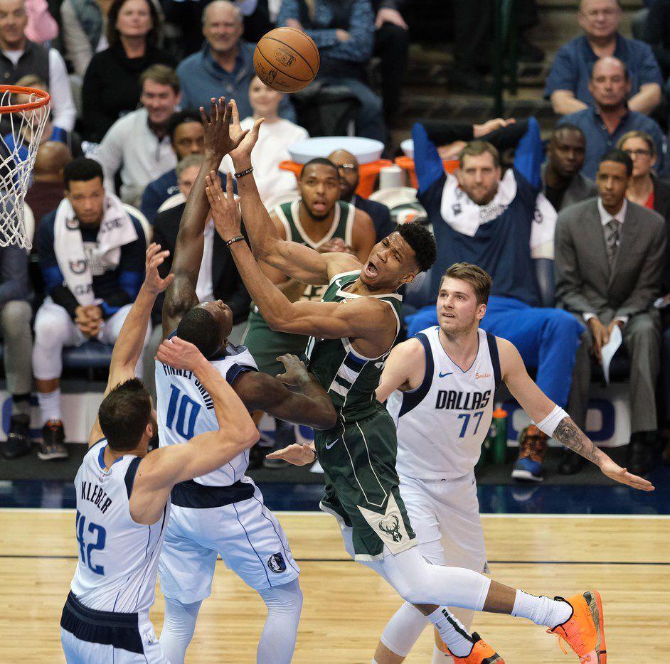 El jugador de los Bucks de Milwaukee, Giannis Antetokounmpo (centro), es observado por el jugador de los Mavericks de Dallas, Luka Doncic (der), en un partido efectuado en el American Airlines Center de Dallas, el 8 de febrero de 2019.