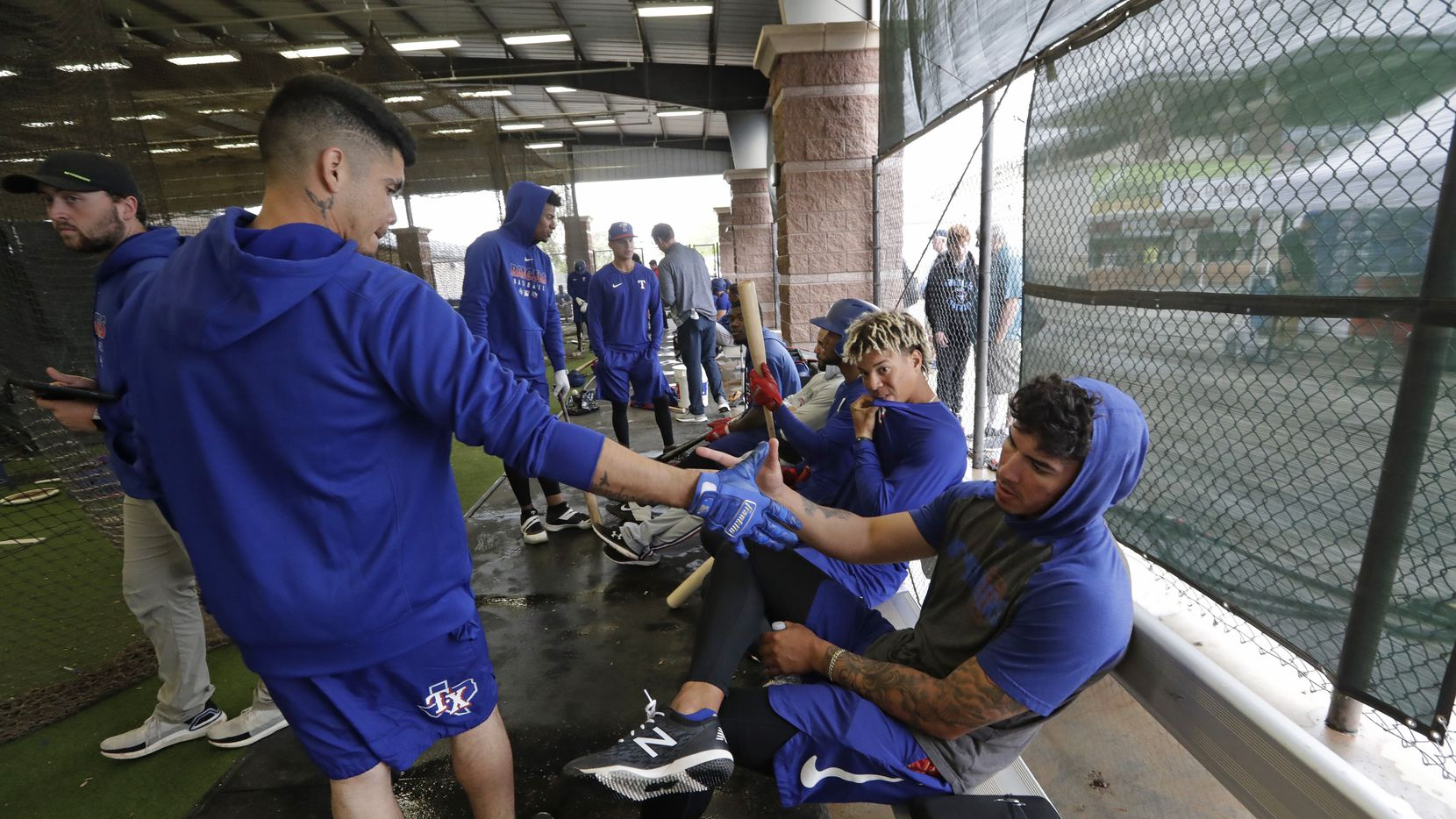 In this March 12, 2020, file photo, Texas Rangers minor-league players Chris Seise, right, and Kevin Mendoza greet each other in the batting cages in Surprise, Ariz.  Spring training could be delayed for Double-A and Class A players if major leaguers are not vaccinated for the novel coronavirus by the time big league practice is scheduled to start in mid-February. Major League Baseball, which has taken over operation of the minors, gave notice to minor league teams and big league clubs Monday, Jan. 4.