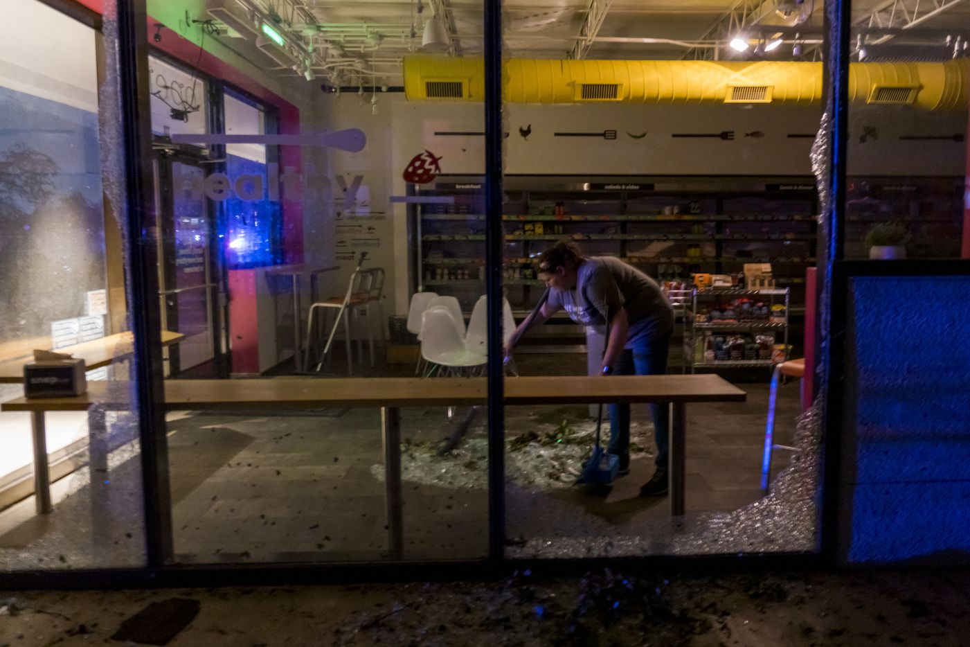 Anna Waugh  cleans up shattered glass from a business after tornado damage near the intersection of Royal and Preston on Sunday, Oct. 20, 2019, in Dallas.