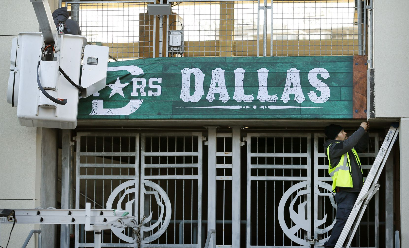 Edgar Pena (right) and Giovani Morales hang a Dallas Stars banner outside the Cotton Bowl in preparation for the New Year's Day Winter Classic hockey game at Fair Park in Dallas, Tuesday, December 17, 2019. The annual game will pit the Dallas Stars against the Nashville Predators.