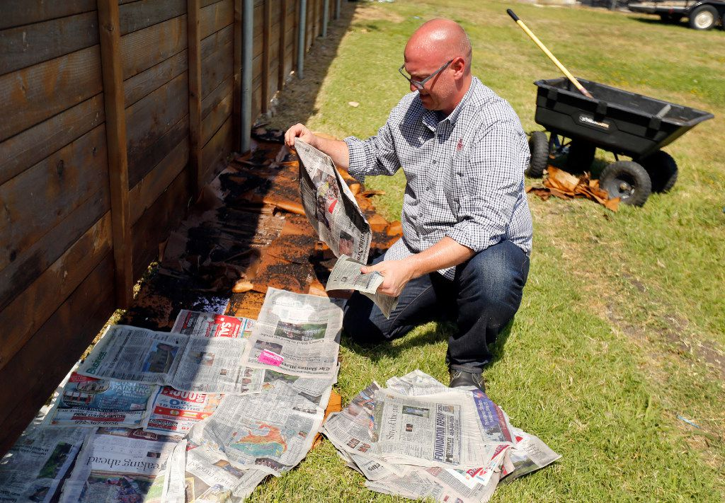 Daniel Cunningham drapes wet newspaper over homemade compost and wet cardboard.