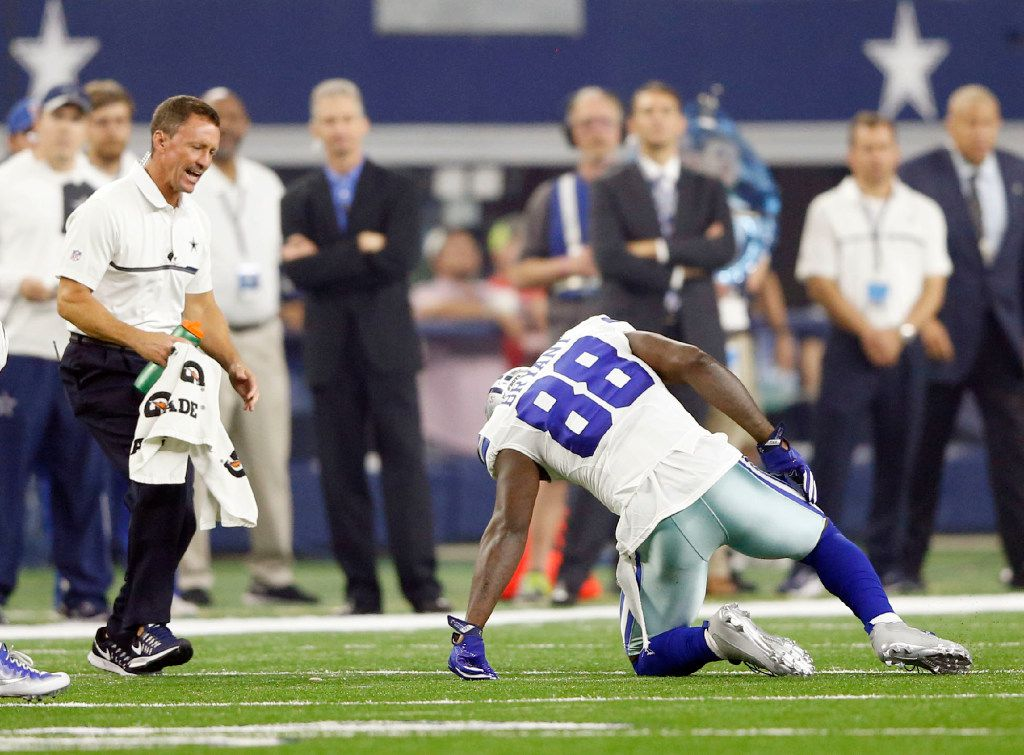 Dallas Cowboys athletic trainer Britt Brown comes to the aid of Dallas Cowboys wide receiver Dez Bryant (88) after he injured his right knee on the opening drive against the Chicago Bears during the first quarter of play at AT&T Stadium in Arlington on Sunday, September 25, 2016. (Vernon Bryant/The Dallas Morning News)
