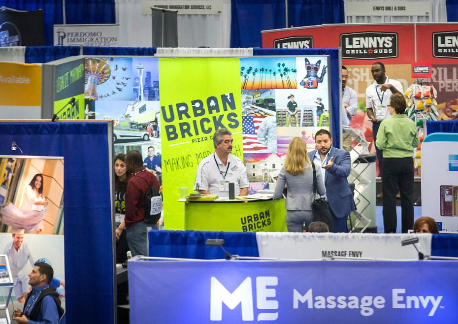 Sammy Aldeeb, founder & CEO of Urban Bricks Pizza Co., gestures at talks to a visitor to the company's booth the at Franchise Expo South Kay Bailey Hutchison Convention Center in Dallas. (Smiley N. Pool/The Dallas Morning News)