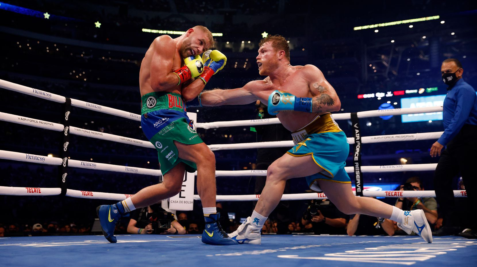 Boxer Canelo Alvarez (right) lands a punch on Billy Joe Saunders during their super middleweight title fight at AT&T Stadium in Arlington, Saturday, May 8, 2021. Saunders couldn't go on in the ninth round because he sustained an eye injury and could not see. (Tom Fox/The Dallas Morning News)