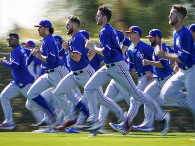 Texas Rangers pitchers, including, from far left, Yohander Mendez, Tyler Phillips, Joe Barlow, Jason Bahr and pitcher Kyle Cody run on a conditioning field during the first spring training workout for pitchers and catchers at the team's training facility on Wednesday, Feb. 12, 2020, in Surprise, Ariz.