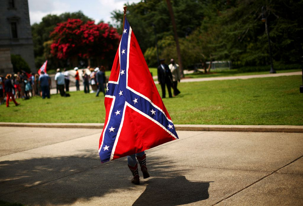 FILE -- A Confederate Battle flag supporter outside South Carolina's State House as the legislature inside considers removing the symbol from the grounds -- they ultimately did -- in Columbia, S.C., July 6, 2015. Sentiment against the divisive flag increased after the massacre of nine black churchgoers in Charleston, but it was often seen at Trump rallies and since his election has materialized at public events and protest marches in the South and beyond. (Travis Dove/The New York Times)