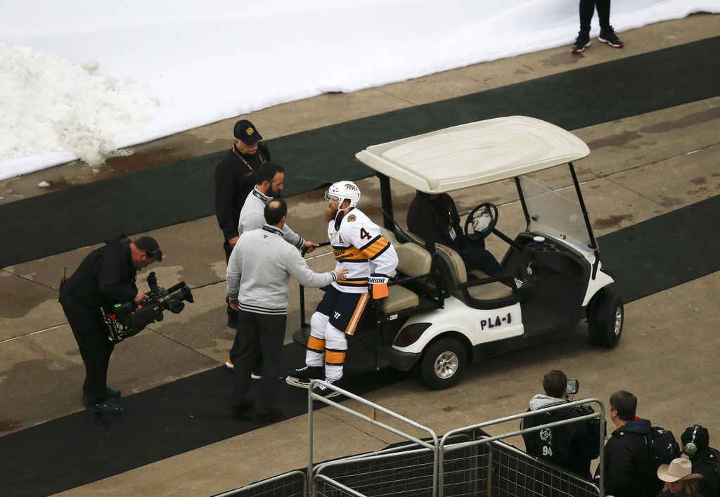 Nashville Predators defenseman Ryan Ellis (4) is helped off the ice after being injured during the first period of a NHL Winter Classic matchup between the Dallas Stars and the Nashville Predators on Wednesday, January 1, 2020 at Cotton Bowl Stadium in Dallas. (Ryan Michalesko/The Dallas Morning News)
