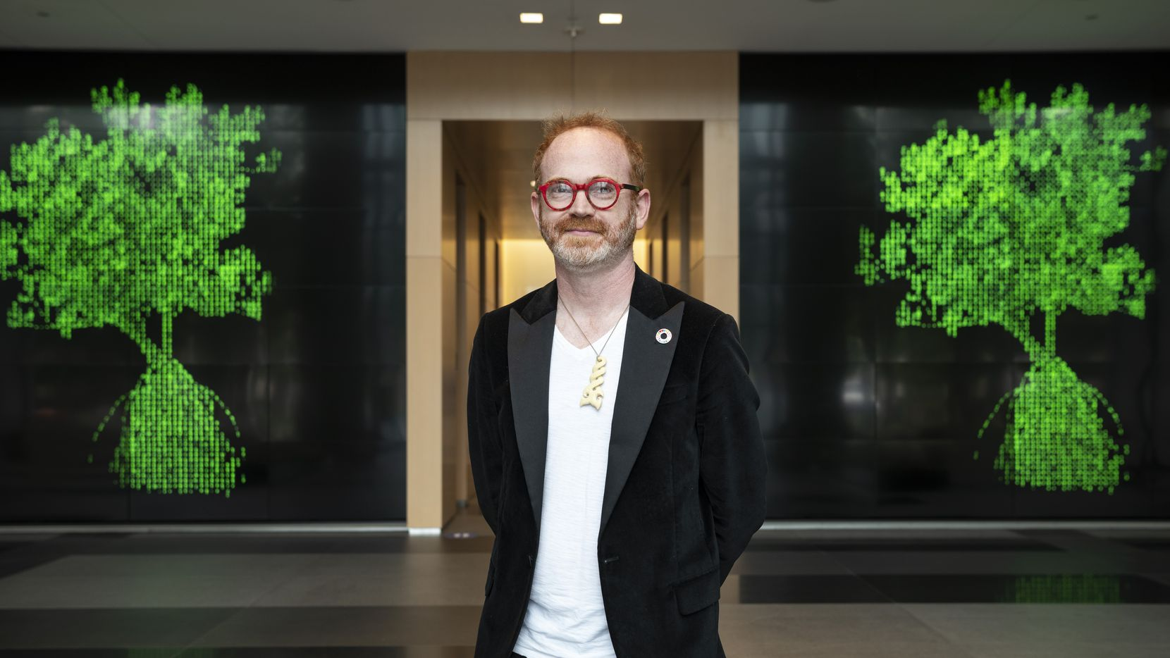 Jeremy McKane, 44, poses in front of two representations of his NFT creations inside the One Arts Plaza building in Downtown Dallas in May.