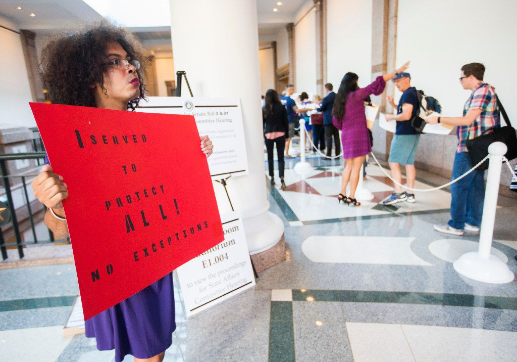 Nicole Lynn Perry, a veteran who is transgender, holds a sign as people stand in line to voice their opinions on the bathroom bill at a public hearing on the fourth day of a special legislative session on Friday, July 21, 2017 at the Texas state capitol in Austin, Texas. (Ashley Landis/The Dallas Morning News)